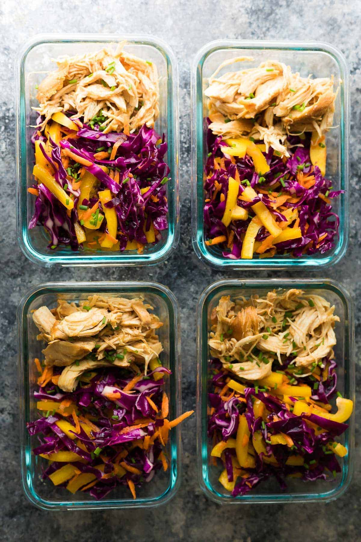 Overhead view of four glass meal prep containers with slow cooker chipotle honey chicken