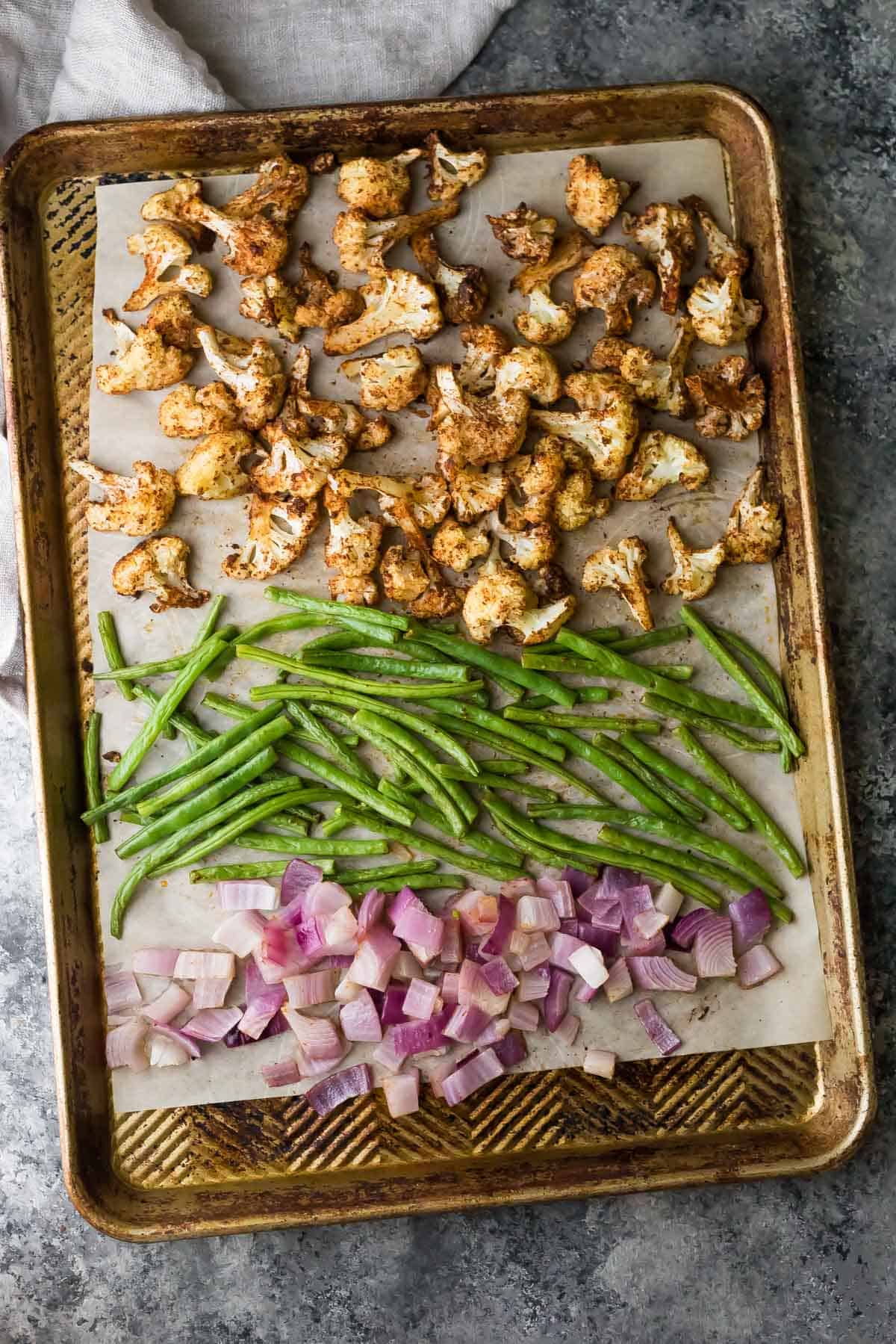 sheet pan with seasoned cauliflower, green beans, and red onion