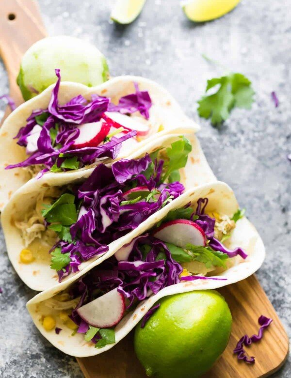 three cilantro lime chicken tacos on wood cutting board with fresh limes