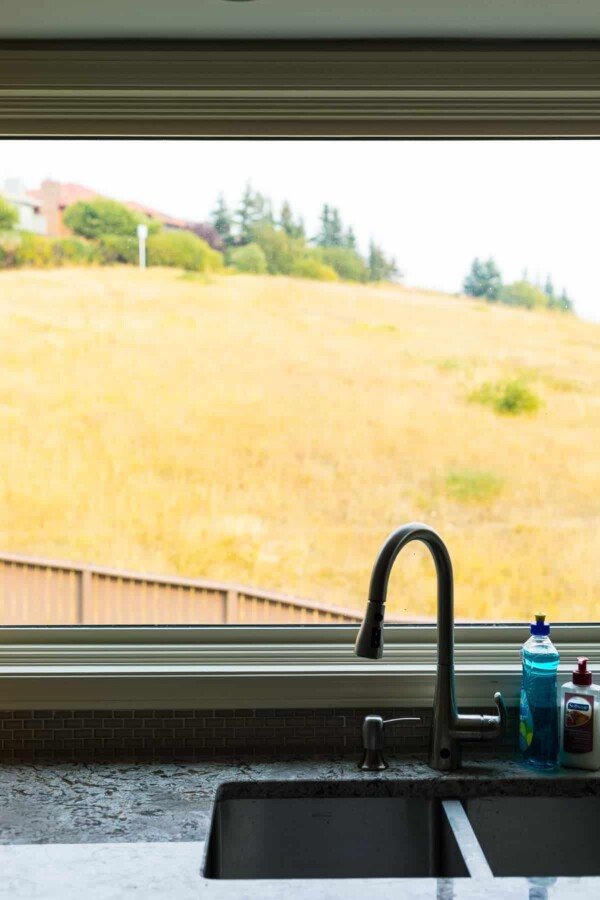 kitchen sink in front of a window with grass in the background