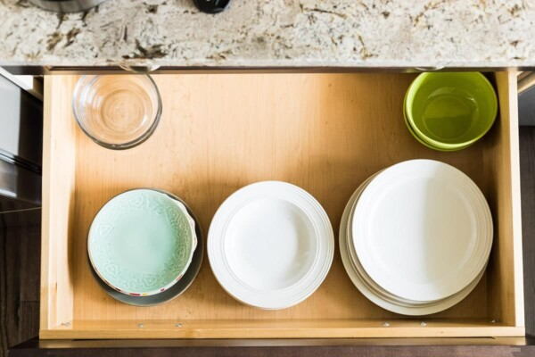 lots of bowls sitting on a wood tray on the counter