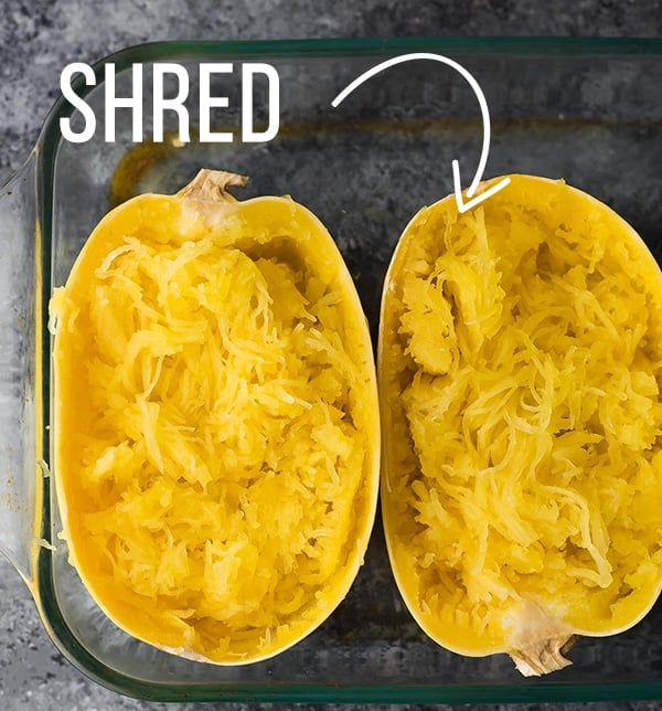 Spaghetti squash in baking dish after baking with flesh shredded