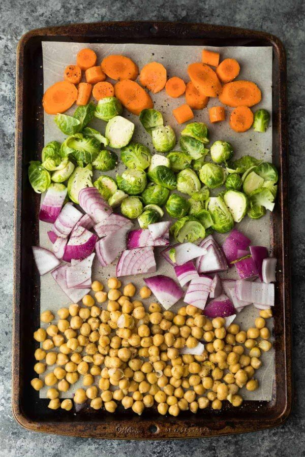 chickpeas, red onion, brussel sprouts, carrots on sheet pan before baking