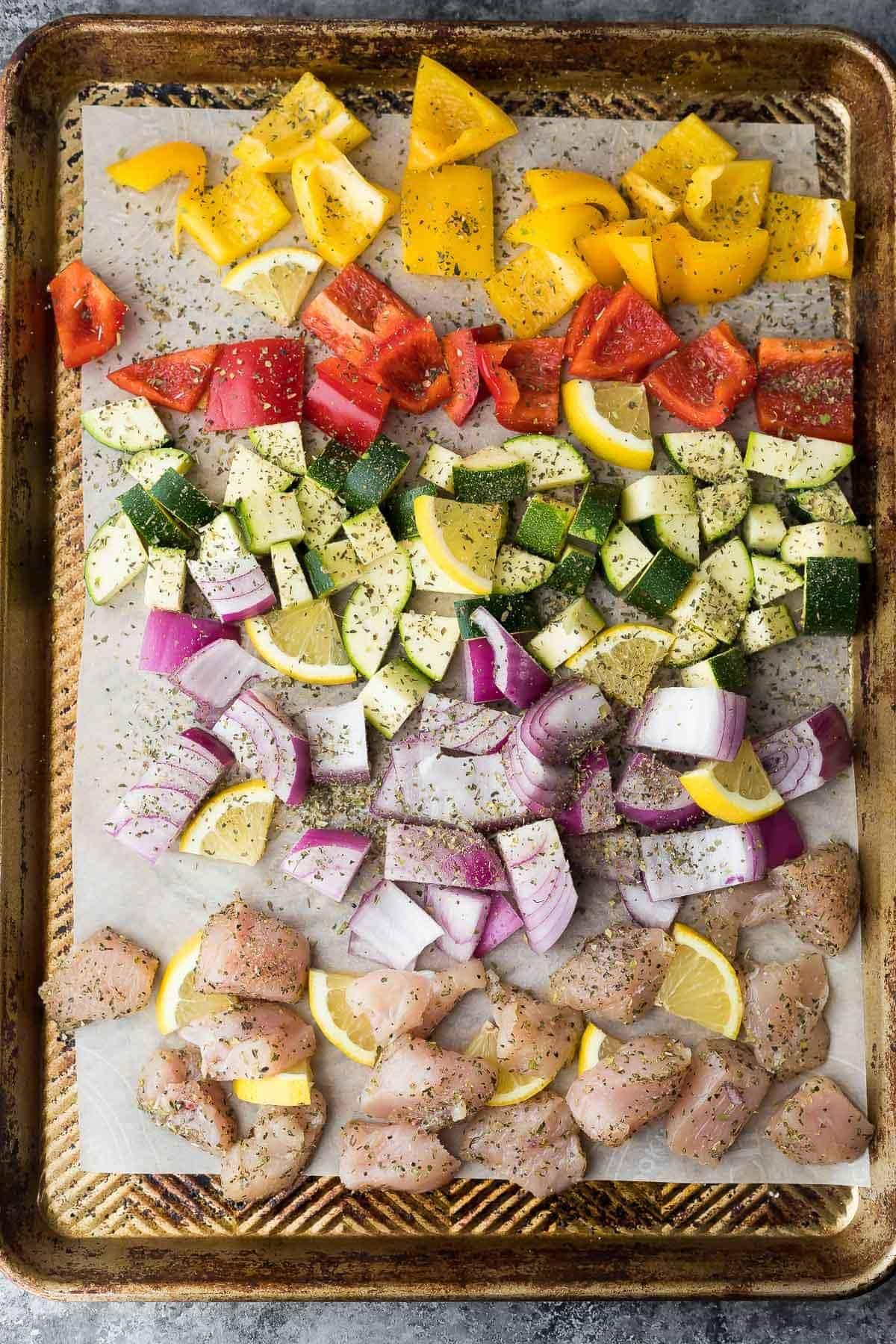 Greek chicken seasoning on a sheet pan sprinkled over raw veggies and chicken