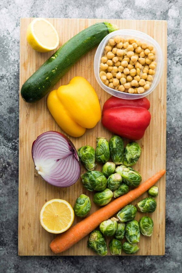 wood cutting board with raw ingredients for Chickpea Buddha Bowls and Greek Chicken Wraps