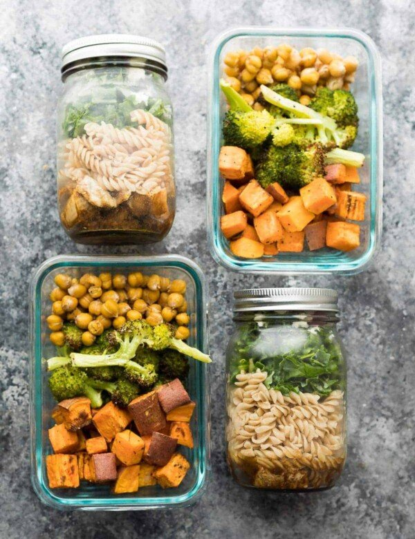 overhead shot of chickepea broccoli and sweet potato balsamic pasta salad in mason jars and glass containers
