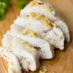 sliced ginger and lemon chicken on wood cutting board