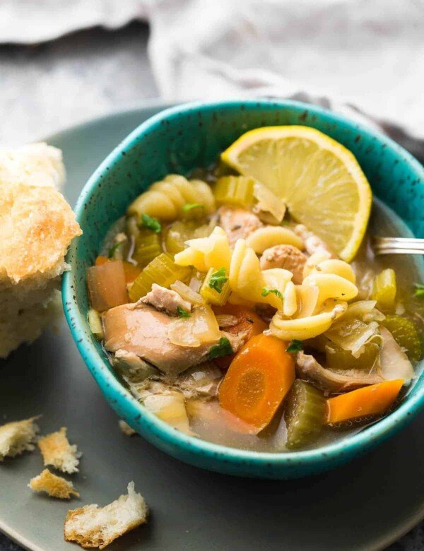 blue bowl with lemon ginger chicken noodle soup with lemon and bread