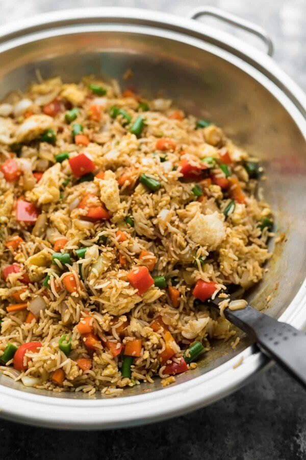 Fried rice in a large wok with spatula