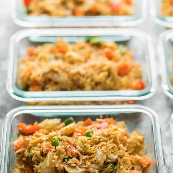 row of glass meal prep containers filled with egg fried rice