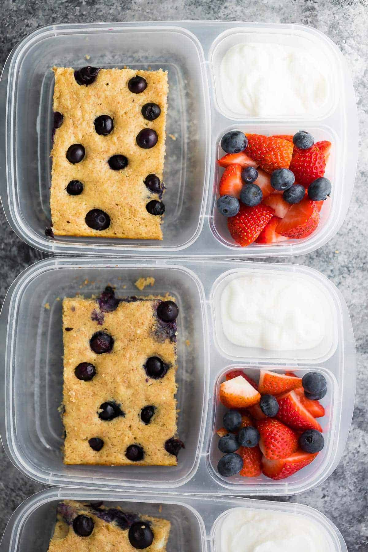 meal prep protein pancakes in three meal prep containers with fresh berries and yogurt