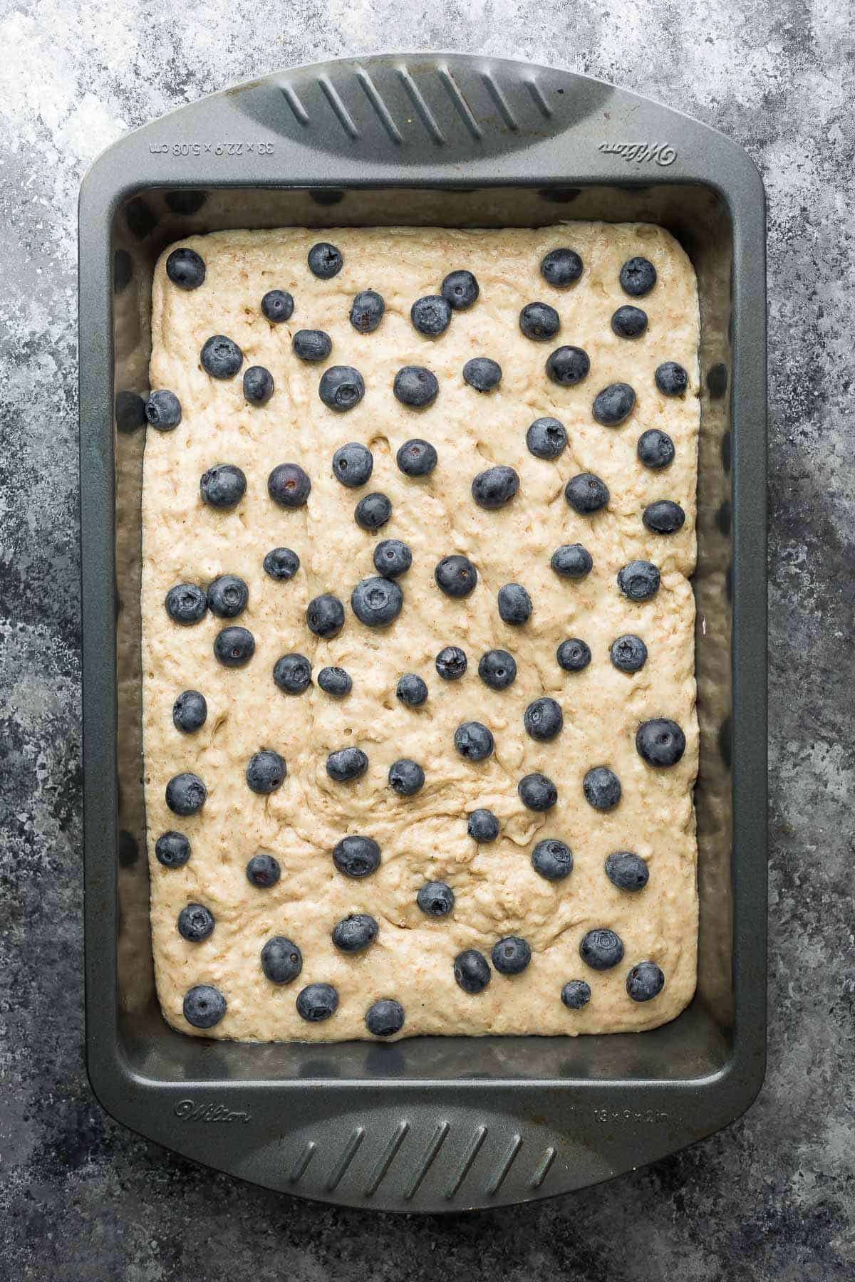 protein powder pancake batter with blueberries in a pan before baking