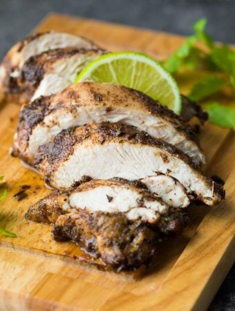 sliced chicken on a wood cutting board with jamaican jerk chicken marinade on it and fresh lime wedges