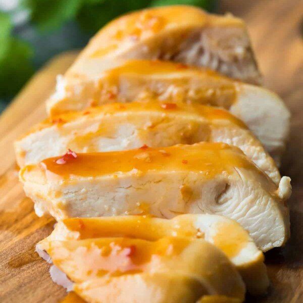 A close up of sliced sweet chili chicken on wood cutting board