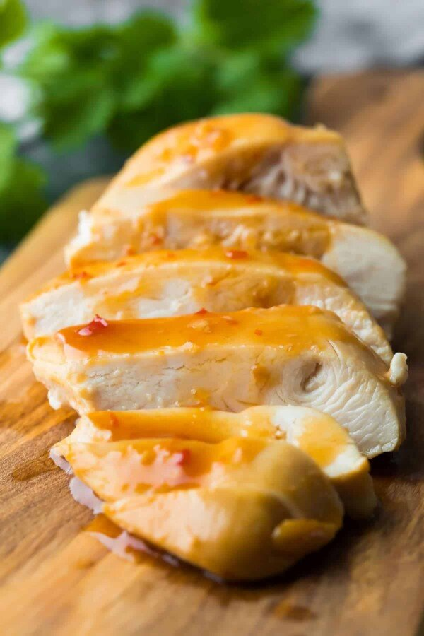 Sweet chili chicken marinade has only two ingredients and can be prepared ahead and frozen. This chicken cooks up in a sauce that you can spoon over the cooked chicken breast or rice and veggies. #sweetpeasandsaffron #chicken #marinade