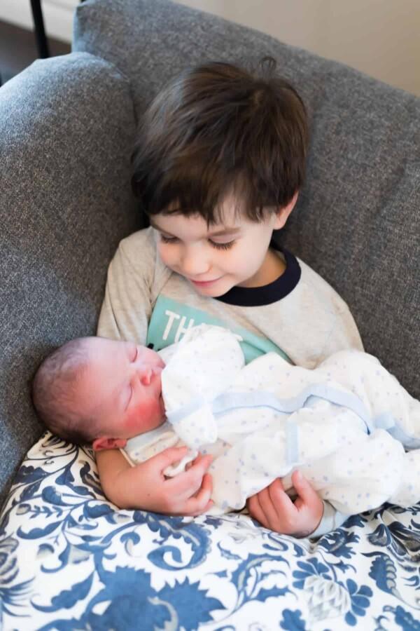 a small boy holding a newborn baby