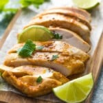 sliced chicken on wood cutting board with fresh limes and chipotle chicken marinade