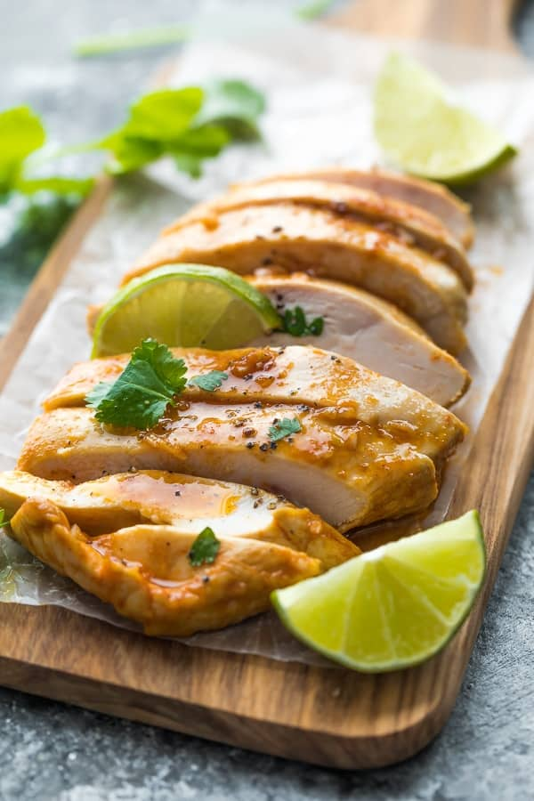 Chipotle chicken sliced on cutting board with lime wedges
