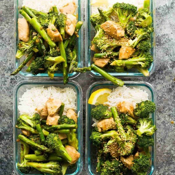 overhead shot of four glass meal prep containers with vegetable and rice stir fry