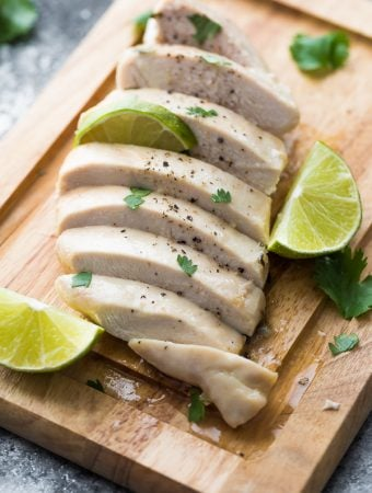 Sliced chicken on wood cutting board with cilantro lime chicken marinade and fresh limes