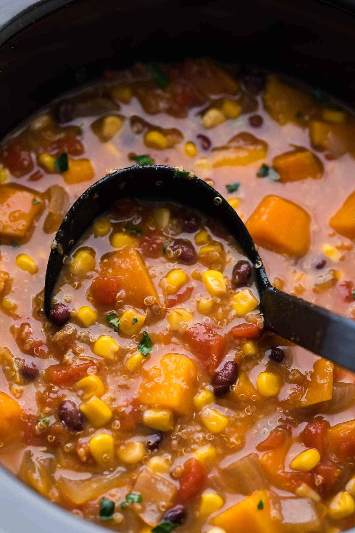 Sweet potato stew in slow cooker with a ladle after cooking