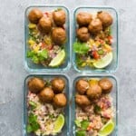 overhead shot of four glass meal prep containers with chipotle honey mealballs, rice and limes