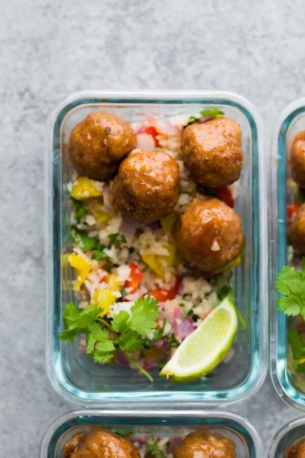 Overhead view of glass meal prep container with honey chipotle meatballs and cilantro lime cauliflower rice