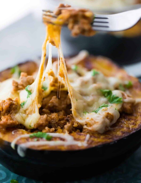 close up of taco stuffed acorn squash with fork taking out a bite of melted cheese