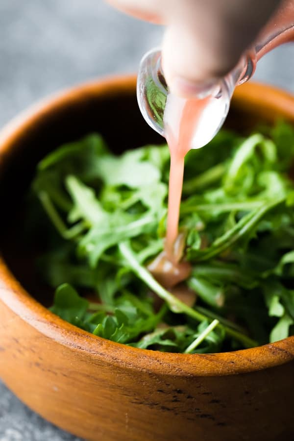 Pouring the red wine vinaigrette dressing over a green salad
