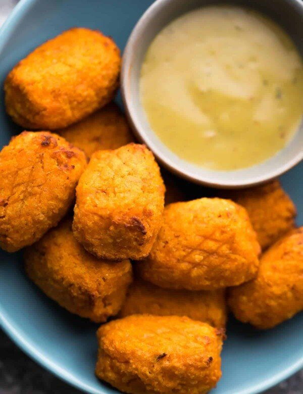 a pile of crispy air fryer sweet potato tots with dipping sauce on blue plate