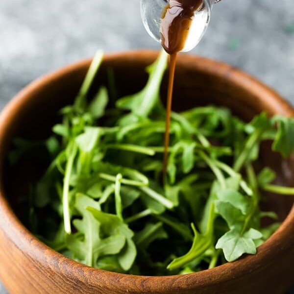 wooden bowl of salad leaves with balsamic vinaigrette being drizzled on top
