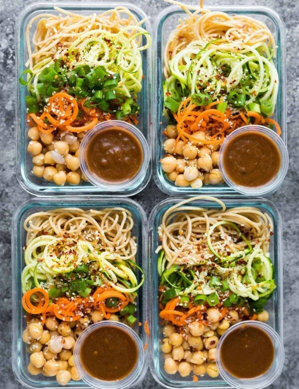 overhead shot of four meal prep containers with sesame noodles and spiralized vegetables