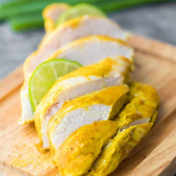 Sliced curry yogurt chicken on a wood cutting board with lime slice