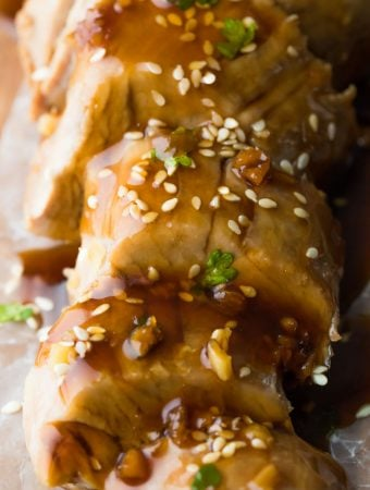Close up shot of sliced instant pot pork tenderloin topped with soy ginger sauce and sesame seeds