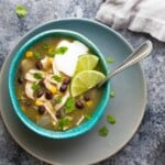 overhead shot of chicken chile verde soup in blue bowl with spoon on gray counter