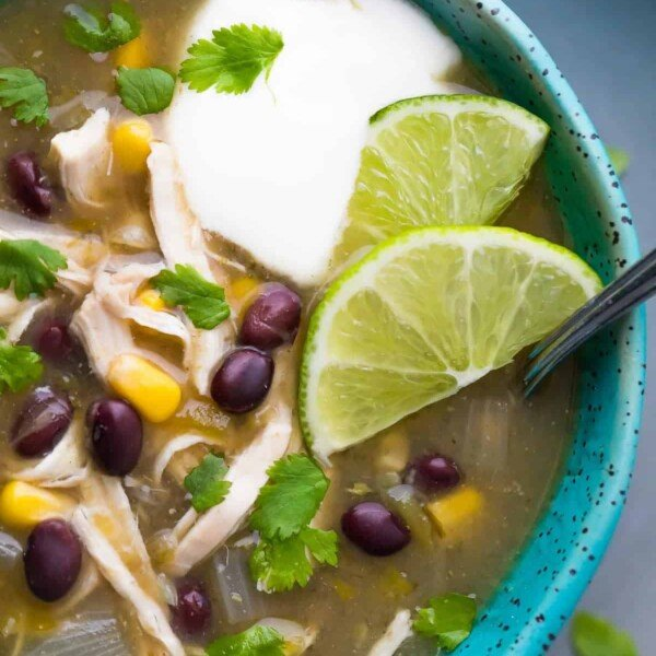close up shot of chicken chile verde soup with lime wedges and sour cream
