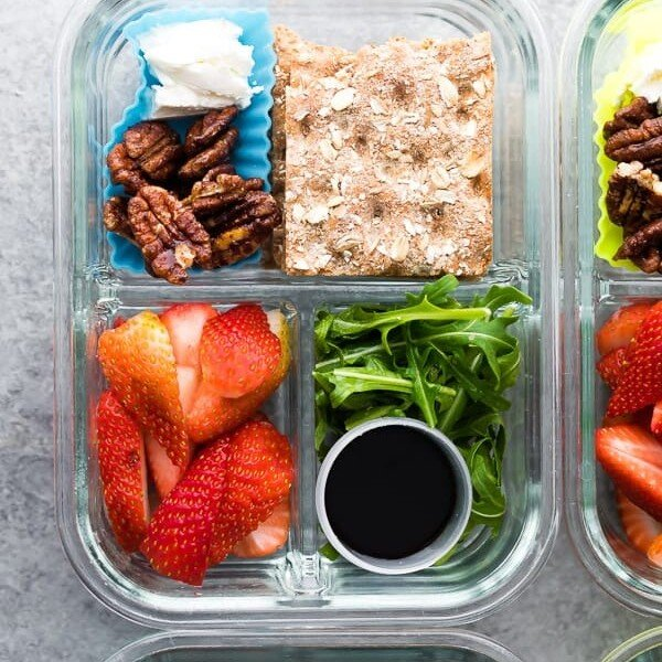 overhead shot of spring strawberry bento box with nuts crackers strawberries and salad in glass meal prep container