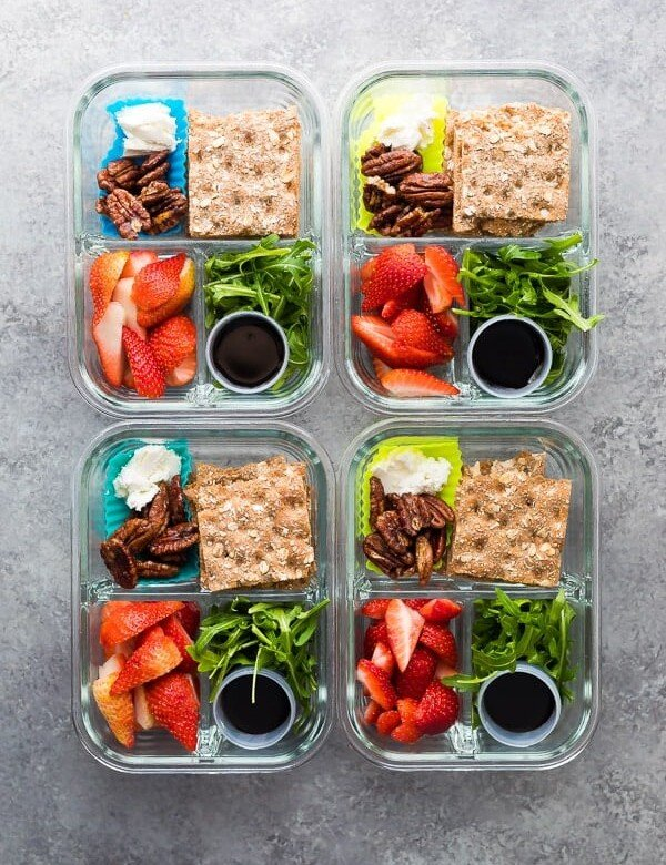 overhead shot of four spring strawberry bento boxes on gray counter