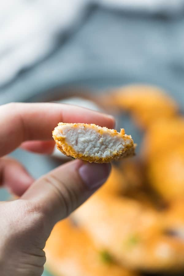 hand holding an air fryer chicken tender cut in two