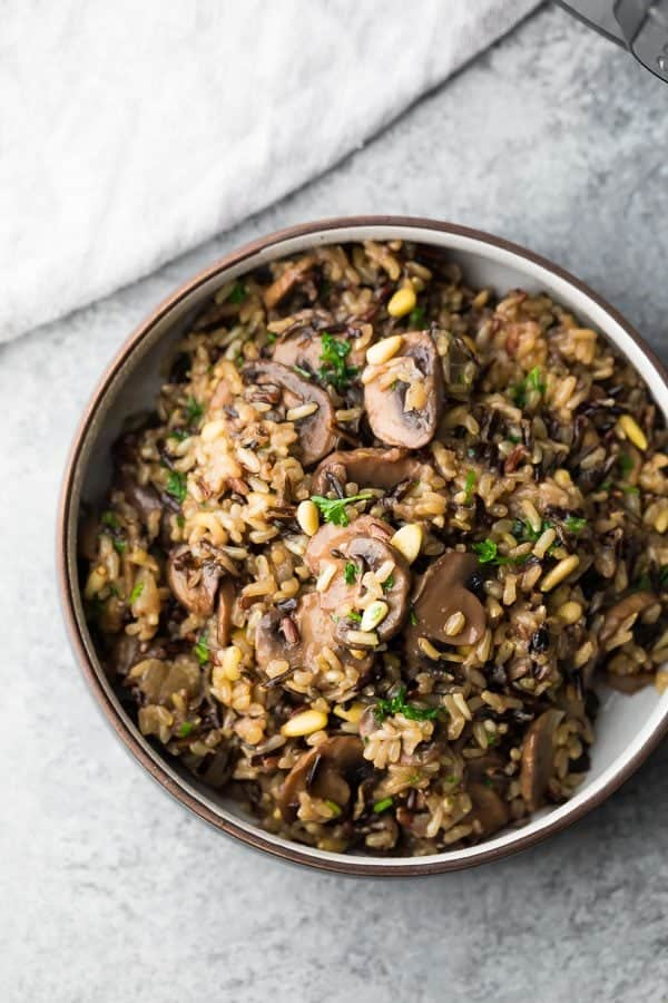 overhead shot of wild rice pilaf in brown bowl sitting on gray counter
