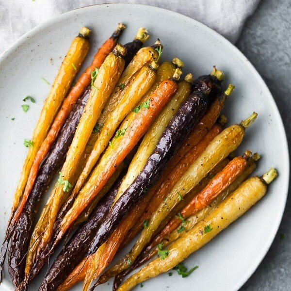 Multi-colored honey roasted carrots on a white plate
