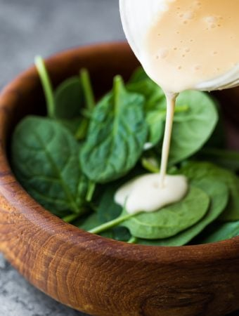 pouring maple tahini dressing onto a salad