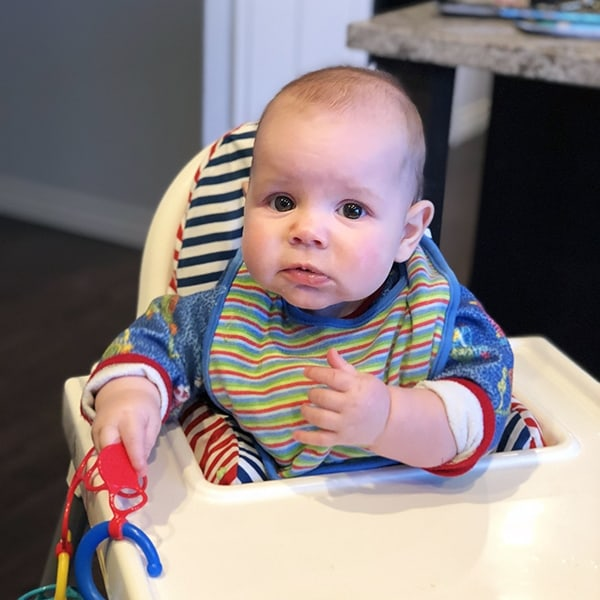 Denise\'s baby sitting in a high chair