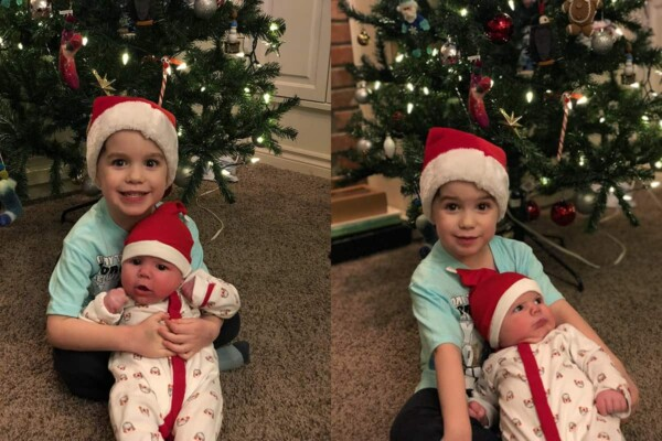two little boys wearing santa hats in front of a christmas tree
