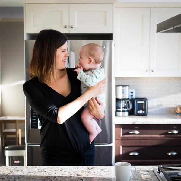 Denise standing in the kitchen with her baby