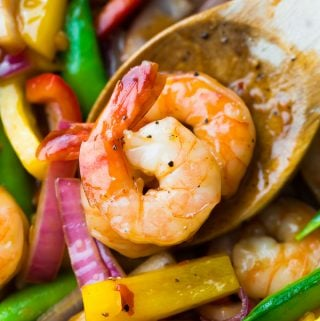 close up shot of wood spoon with two shrimp on it in sweet chili stir fry
