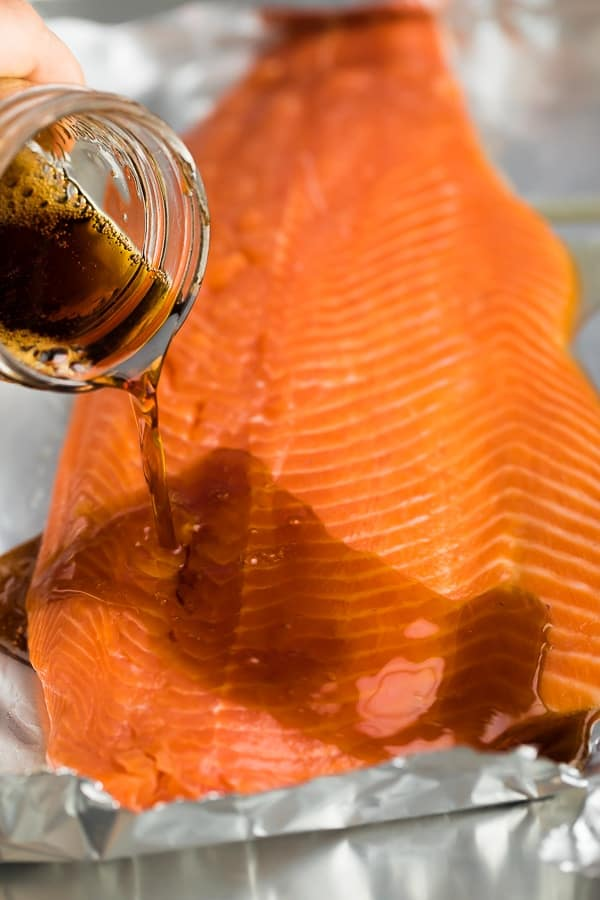 pouring the maple soy marinade over the salmon