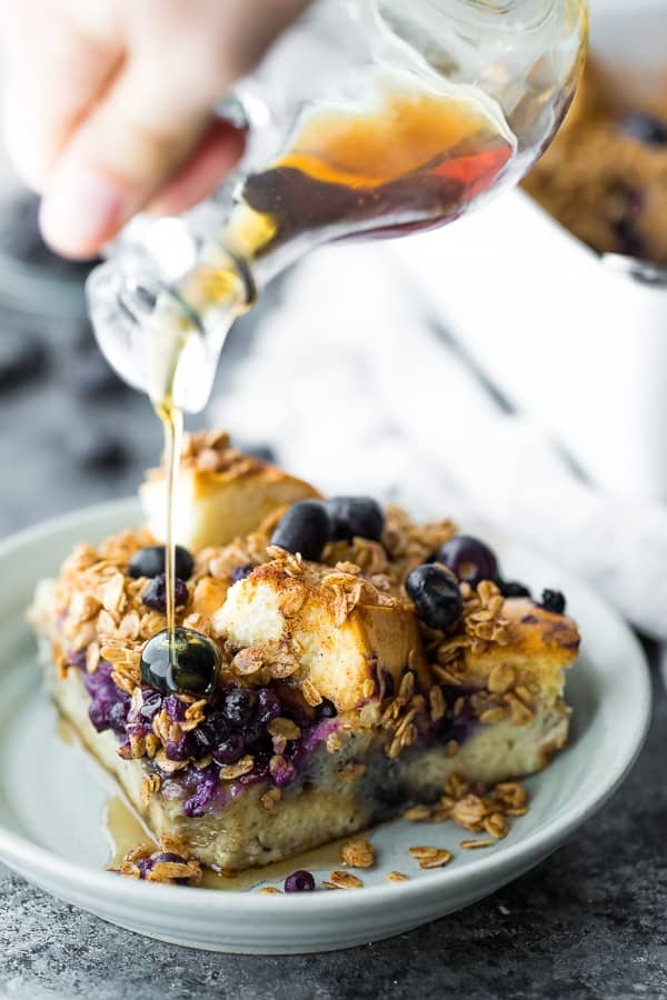 pouring maple syrup onto the blueberry overnight french toast bake