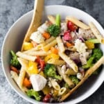Overhead shot of healthy Greek chicken pasta salad in a white bowl with wooden spoon