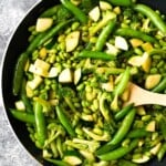 ginger teriyaki stir fry with broccoli snap peas and greens in skillet with wood spoon